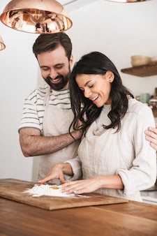 Portrait of caucasian couple man and woman 30s wearing aprons cooking pastry with flour and eggs in kitchen at home