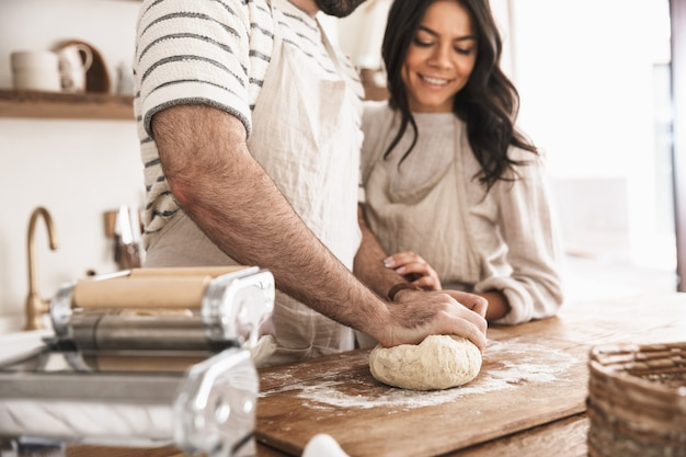 Portrait of caucasian couple man and woman 30s wearing aprons mixing the dough while cooking together in kitchen at home