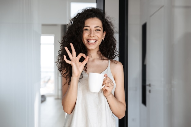 Portrait of caucasian curly woman with long dark hair smiling, and showing ok sign, while drinking tea at hotel apartment or flat in morning
