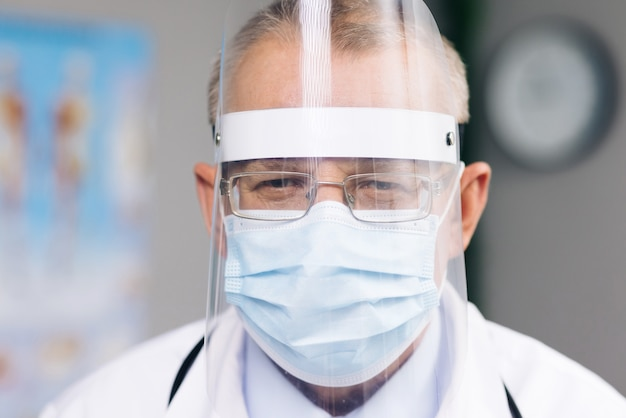 Portrait of a caucasian doctor in glasses is wearing a transparent protective face shield mask and overalls in a hospital room