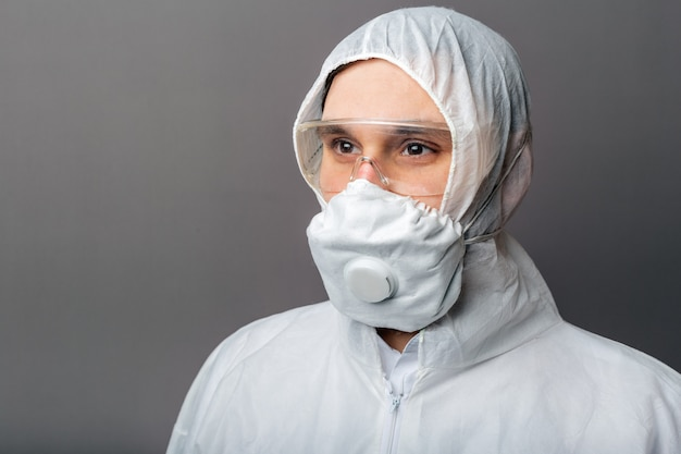 Portrait caucasian doctor in protective medical suit, biological hazard, medical mask ffp3,goggles. doctor in chemical protection clothing for coronavirus covid-19 disinfection.