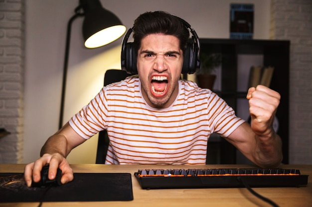 Portrait of caucasian excited gamer guy shouting while looking at monitor, wearing headphones and using backlit colorful keyboard