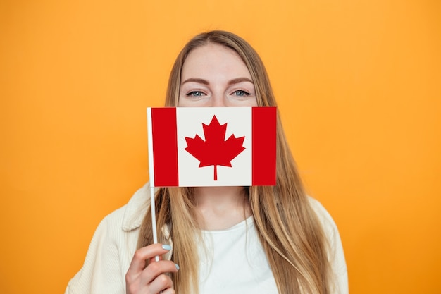 Portrait of caucasian female student covering her face with small canadian flag and looking to camera isolated over orange wall