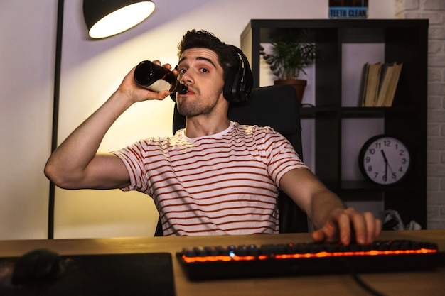 Portrait of caucasian gamer guy wearing headphones drinking beer, while sitting at desk with computer in room and looking at camera