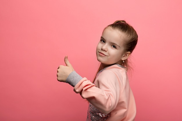 Portrait of a caucasian girl in the studio on a pink isolated background that shows gestures with hands
