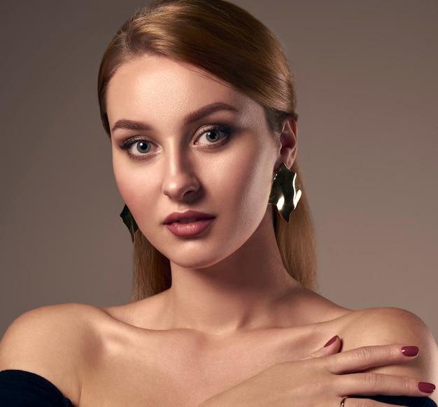 Portrait of caucasian girl wearing wavy modern design earrings and off shoulder dress