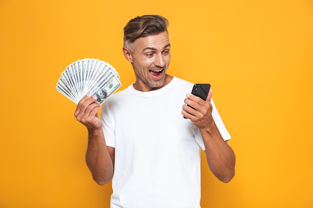 Portrait of caucasian guy 30s in white t-shirt holding cell phone and bunch of money isolated on yellow