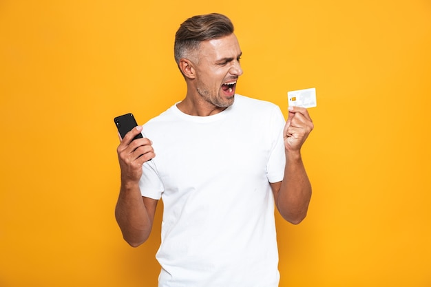 Portrait of caucasian guy 30s in white t-shirt holding mobile phone and credit card isolated on yellow