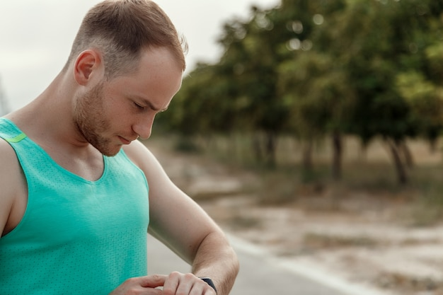 Portrait of caucasian guy in azure t-shirt looking at fitness tracker readings