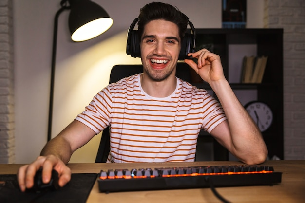 Portrait of caucasian guy wearing headset smiling, while sitting at desk with computer in room and looking at monitor