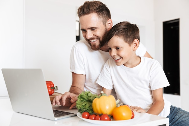 Portrait of caucasian healthy father and son smiling, and reading recipe on laptop for cooking meal with vegetables