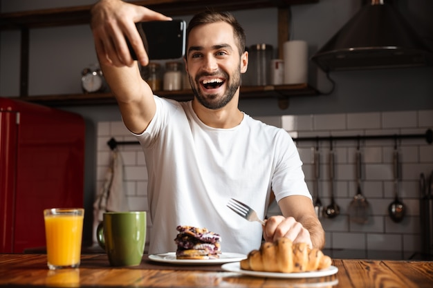 Portrait of caucasian man 30s taking selfie photo on mobile phone while having breakfast in stylish kitchen at home