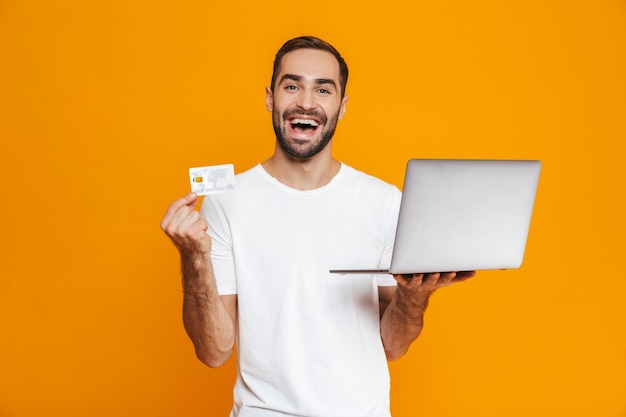 Portrait of caucasian man 30s in white t-shirt holding silver laptop and credit card, isolated