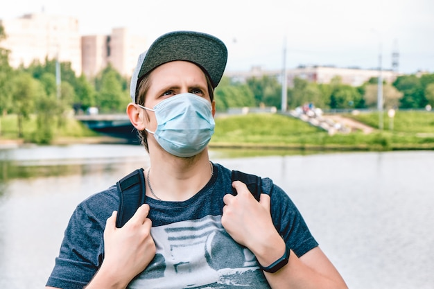 Portrait of a caucasian man in a medical mask during a pandemic in the city. new normal.