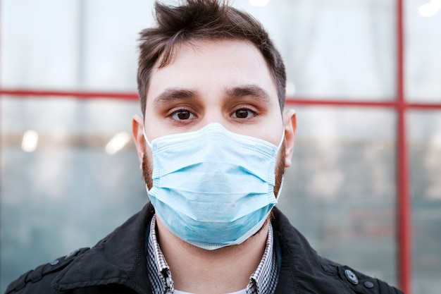 Portrait of caucasian man wearing facial hygienic face mask outdoors. virus, coronavirus protection, air pollution