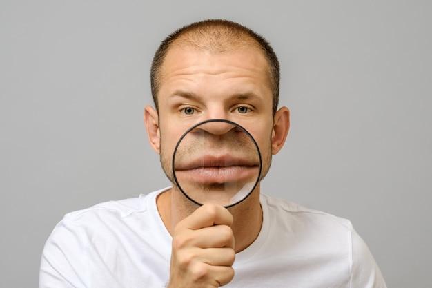 Portrait of caucasian man with magnifier makes fun face