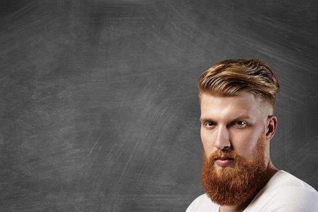 Ritratto di uomo caucasico con taglio di capelli elegante e grande barba sfocata che indossa una maglietta bianca, con espressione pensierosa pensierosa mentre in piedi contro la lavagna vuota