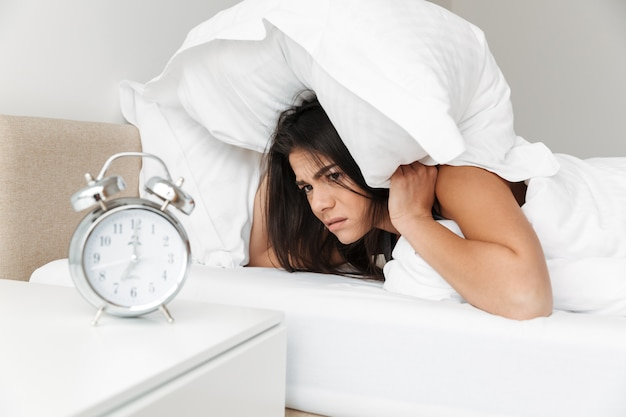 Portrait of caucasian sleepy woman shutting ears with white pillow and looking on ringing alarm clock, while lying at bedroom in morning