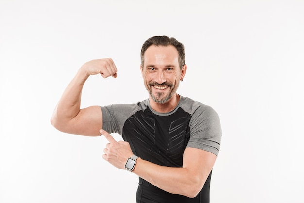 Portrait of caucasian sportsman 30s wearing smartwatch and t-shirt smiling and showing his bicep after training