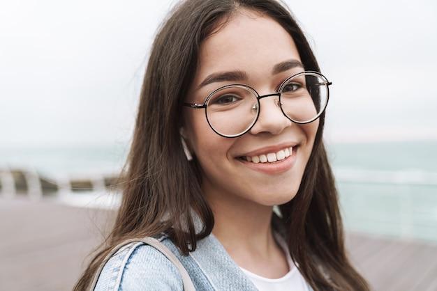Portrait of caucasian teenage girl wearing earpods and eyeglasses laughing while walking along wooden pier by seaside