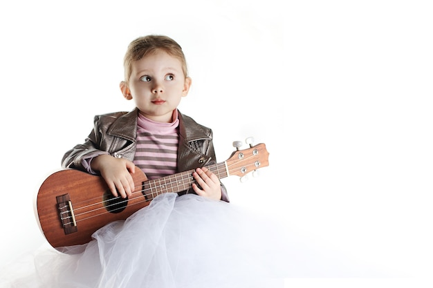 A portrait of caucasian toddler girl with ukulele on white background.