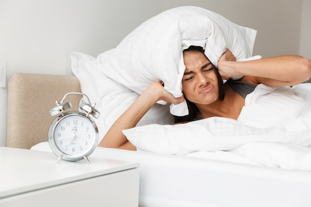Portrait of caucasian upset woman shutting ears with pillow due to ringing alarm clock while lying in bed