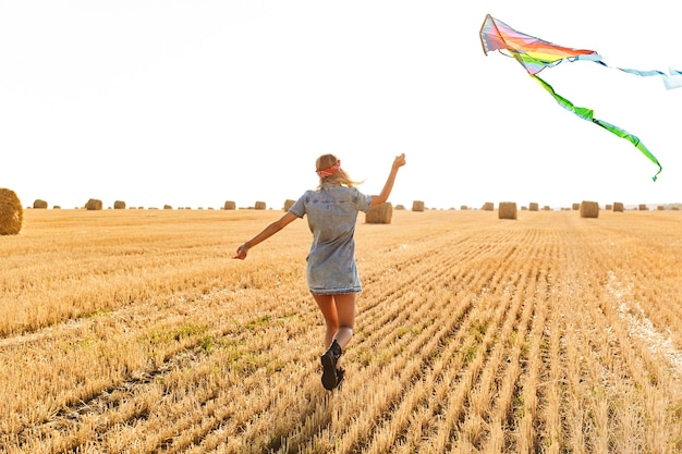 Portrait of caucasian woman 20s smiling and playing with flying kite during walk through golden field, during sunny day