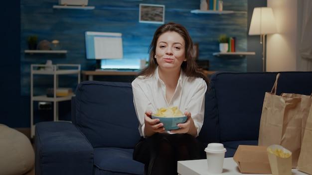 Ritratto di donna caucasica che mangia patatine dalla ciotola Foto Gratuite