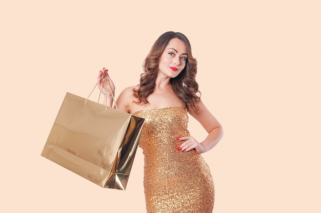 Portrait of caucasian woman in golden dress with golden paper bags on a beige background