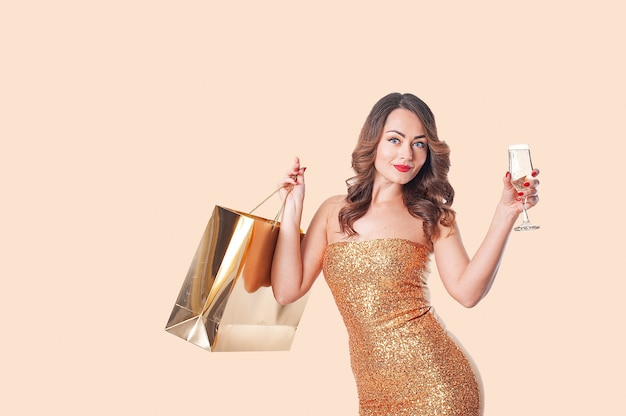 Portrait of caucasian woman in golden dress with golden paper bags and a glass of sparkling wine on a beige background