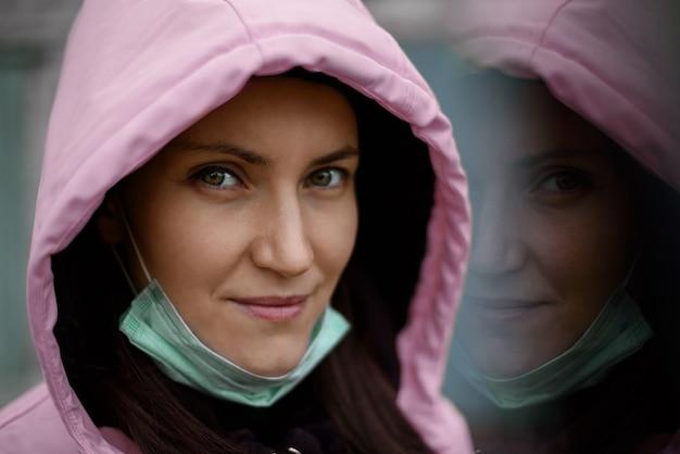 Портрет кавказской женщины в медицинской маске, розовой куртке на открытом воздухе
