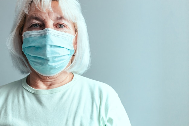 Portrait of caucasian woman in a medical mask isolated on a grey wall background.