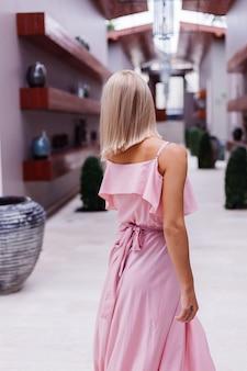 Ritratto di donna caucasica in romantico abito lungo rosa elegante in vacanza presso lussuoso hotel villa ricca con incredibili palme tropicali vista donna nel classico cappello bianco