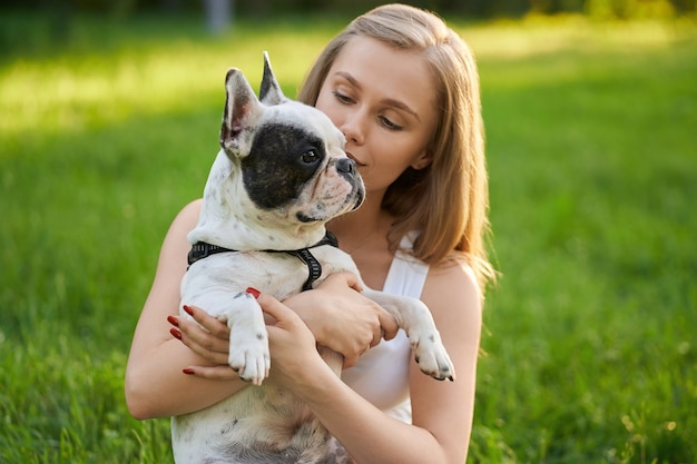 Portrait of caucasian young woman holding adult french bulldog in summer park. blonde female dog owner posing with lovely white and brown purebred pet wearing black leash, looking aside.