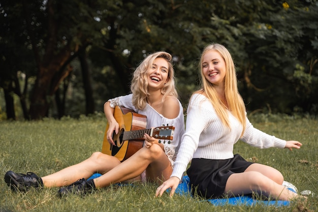 Portrait of caucasian young women sitting in the park outdoor and playing a guitar sing a song together with happiness