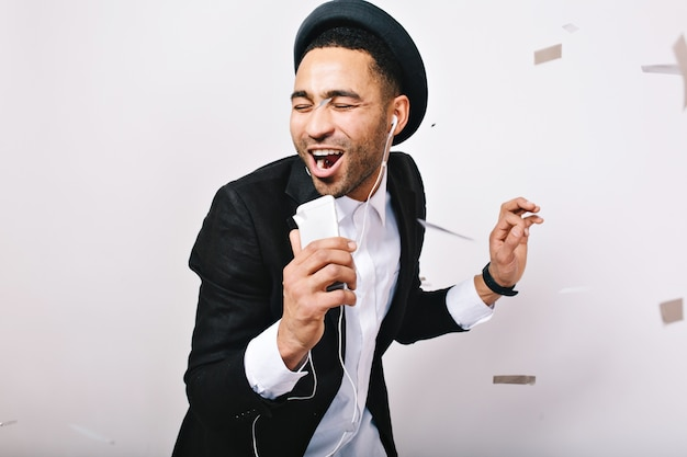 Portrait celebrating karaoke party, happy weekends of excited handsome guy in suit, hat having fun. fashionable look, singer, music, songs, enjoying, expressing positivity.