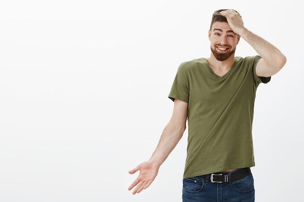 Ritratto di carismatico bell'uomo barbuto scusandosi per il ritardo, dimenticando il tempo tenendo la mano sulla testa colpevole alzando le spalle carino e tenendo la mano lateralmente, sorridendo come scusa