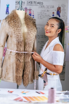 現代のアトリエショップで幸せな肖像画の魅力的なアジアのファッションデザイナーや女性の笑顔を仕立てる