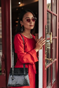 Portrait of charming attractive woman in red dress, stylish sunglasses opens wooden door and holds black handbag