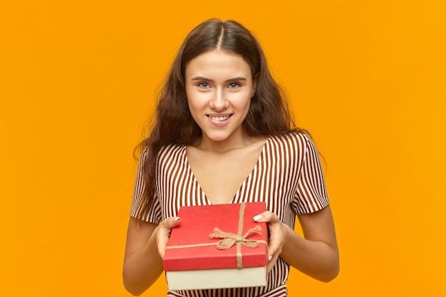 Ritratto di affascinante attraente giovane femmina europea in bel vestito che tiene scatola rossa fantasia con la caramella