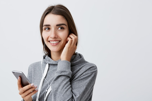 Portrait of charming beautiful brunette caucasian student girl with long hairstyle in stylish gray hoodie smiling with teeth, holding smartphone in hand, listening favorite song in headphones
