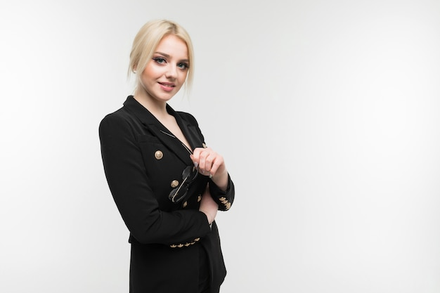 Portrait of charming blonde in black costume possing with glasses on background