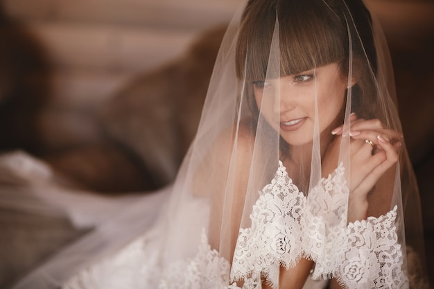 Portrait of charming bride sitting on the bed in a hotel room. the bride is covered with veil. close up. wedding morning. gentle, tender emotion on the face.