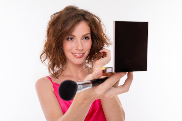 Portrait of a charming brunette with cosmetics in her hands on a white background, beauty industry blogger