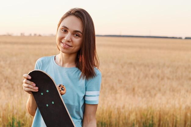 Ritratto di affascinante donna bruna che indossa una maglietta blu guardando direttamente la telecamera, tenendo lo skateboard in mano, copia spazio per la pubblicità, stile di vita sano.