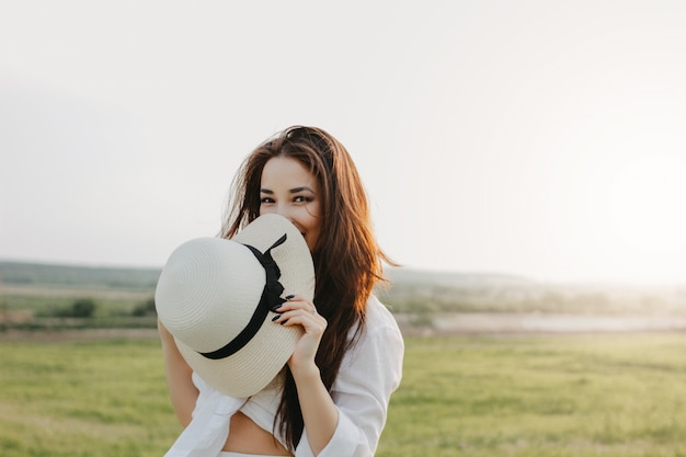Portrait of charming carefree long hair asian girl in white clothes and straw hat enjoys life in nature field