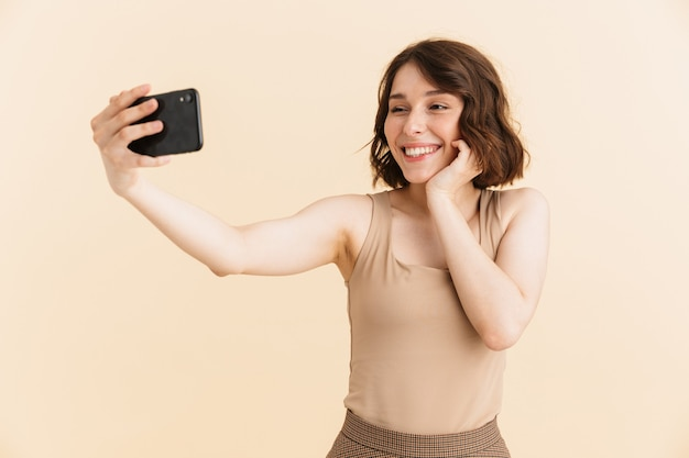 Portrait of charming caucasian woman 20s dressed in casual clothes smiling while taking selfie photo on cellphone isolated