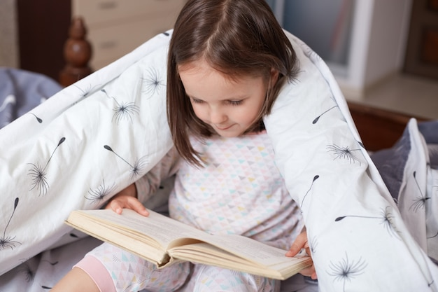 Portrait of charming child reading book at home, wrapped white blanket with dandelions, dark haired kid wearing pajama looking concentrated down on pages from her book.