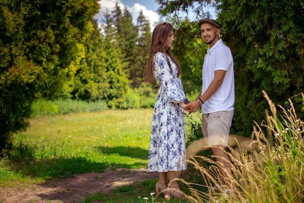 Portrait of charming couple in love hugs and holds hands at the green garden