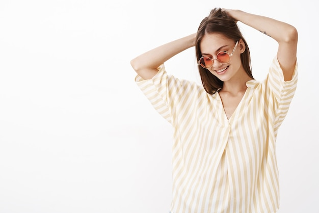 Portrait of charming creative and stylish young female brunette in awesome sunglasses making haircut with hands on head